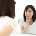 鏡で歯をチェックする笑顔の女性