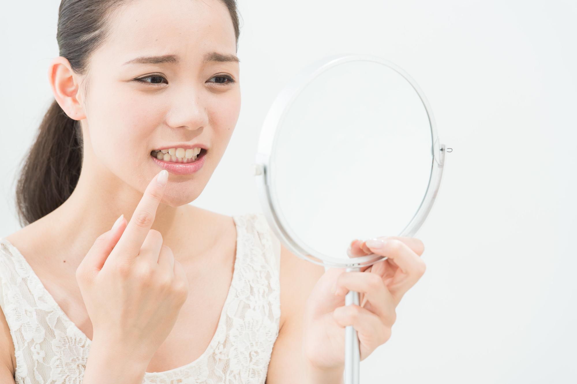 鏡を見て歯を気にする女性