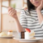 ケーキを食べるか迷う女性