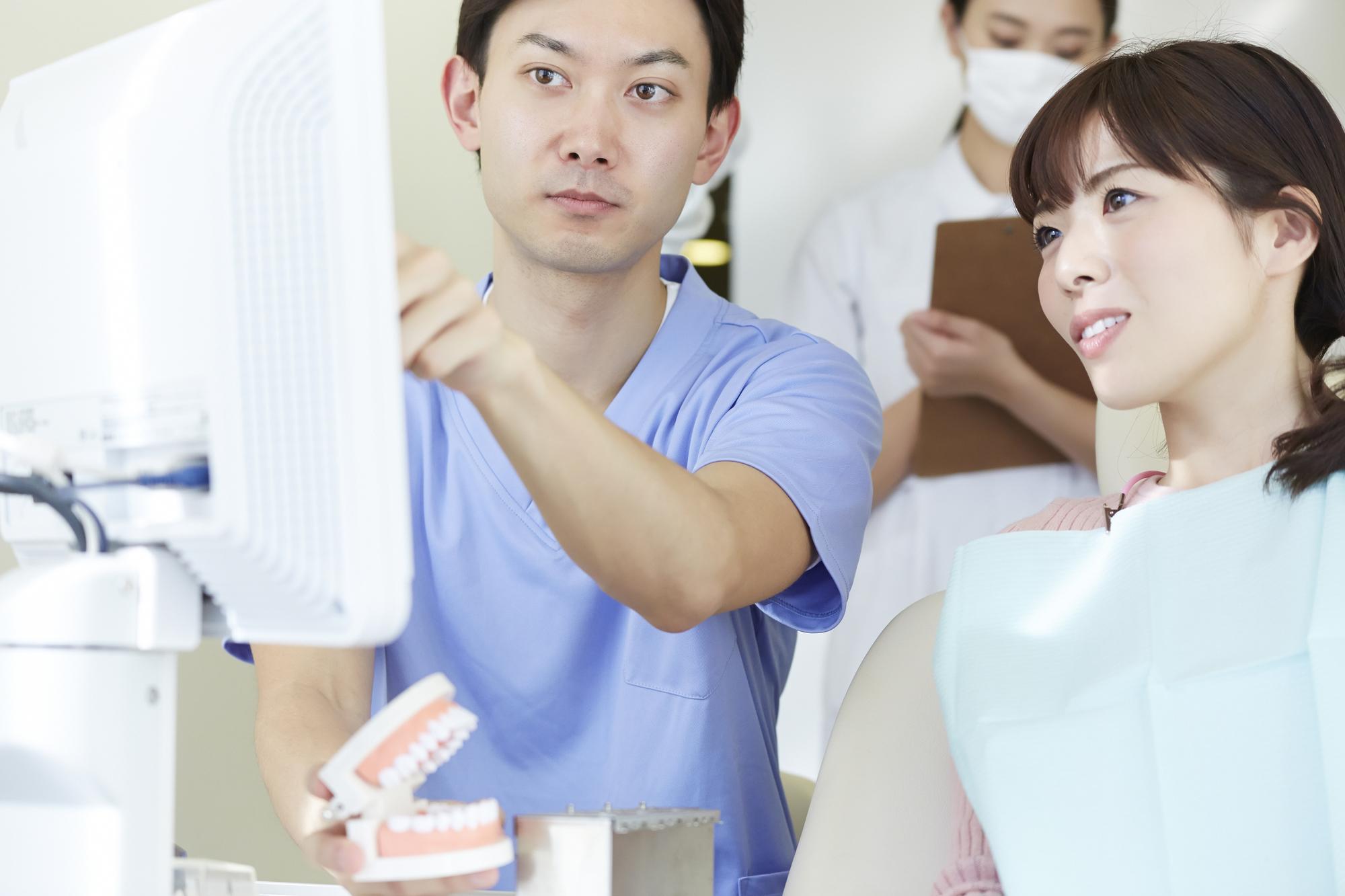 歯科治療の説明を聞く女性患者