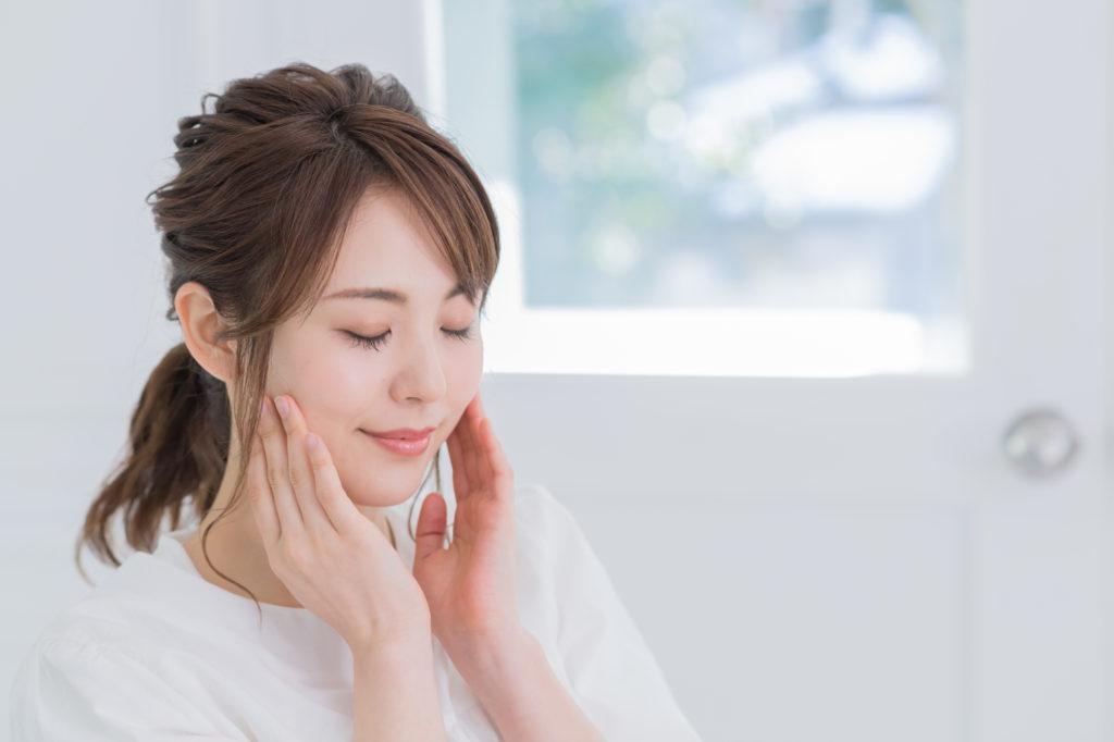 歯の痛みを取り除くために顔のマッサージをする女性