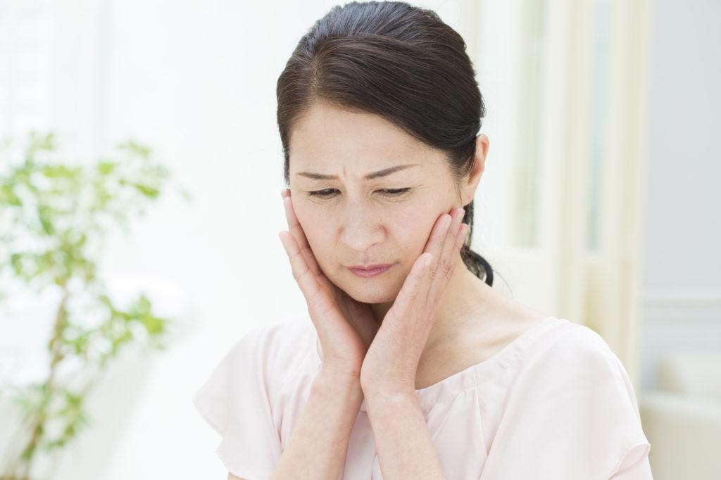 ストレスが原因で歯に痛みを感じる女性の写真