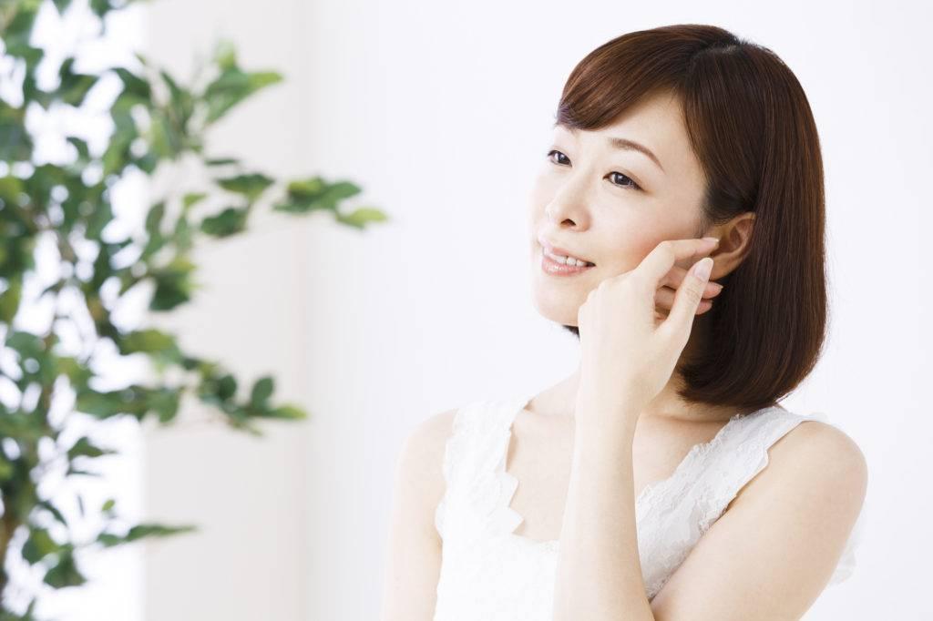 慢性的な痛みに対し顎を温める女性