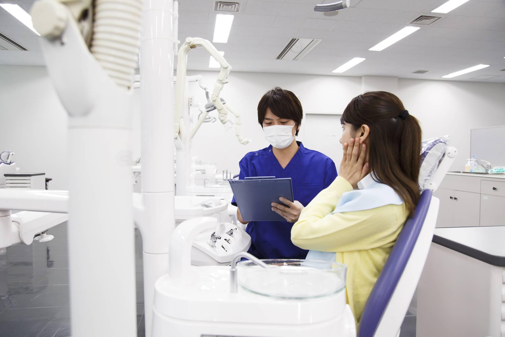 根管治療後の痛みについて相談する女性患者
