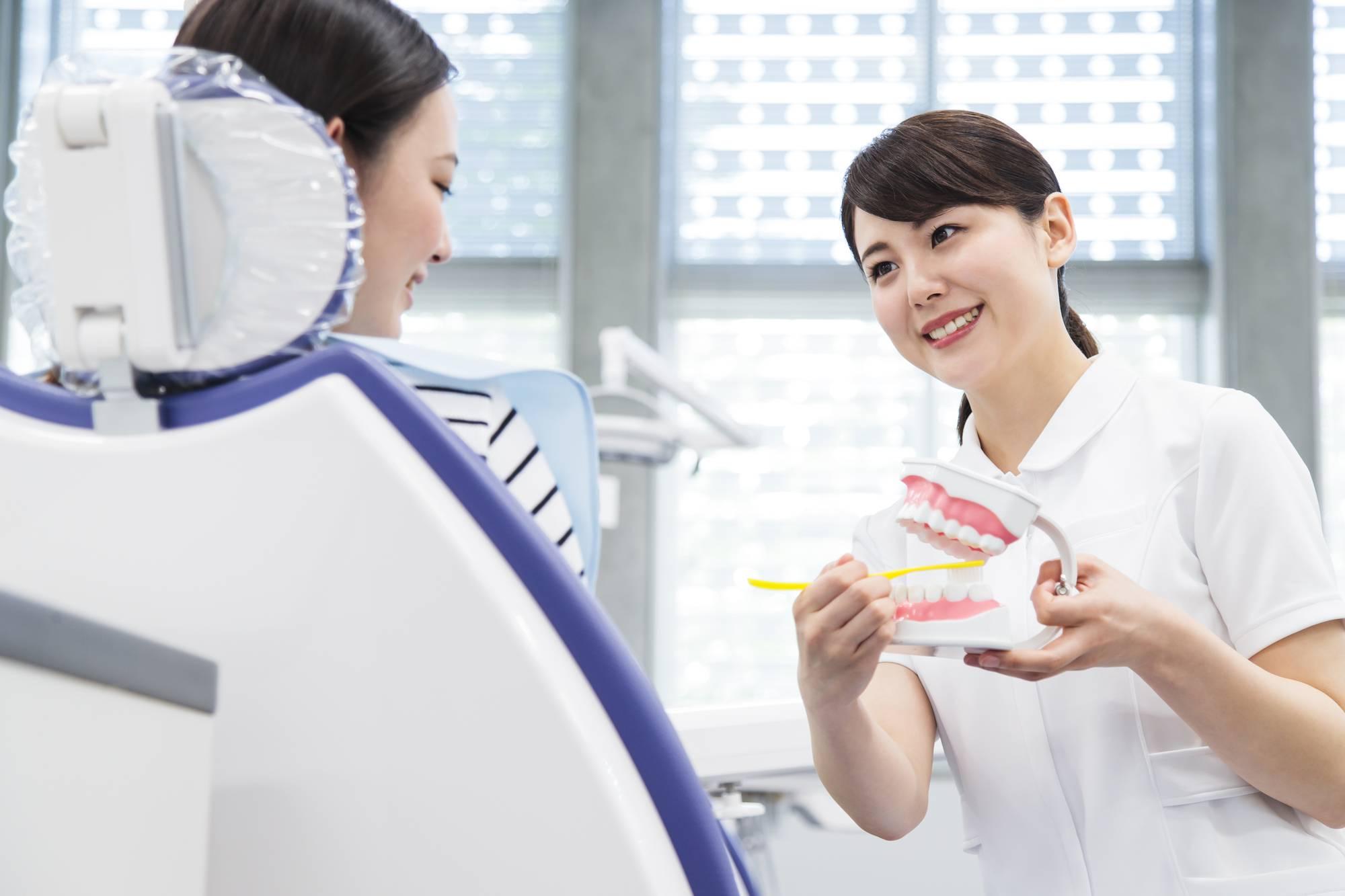 歯科衛生士から歯磨きの指導を受ける女性