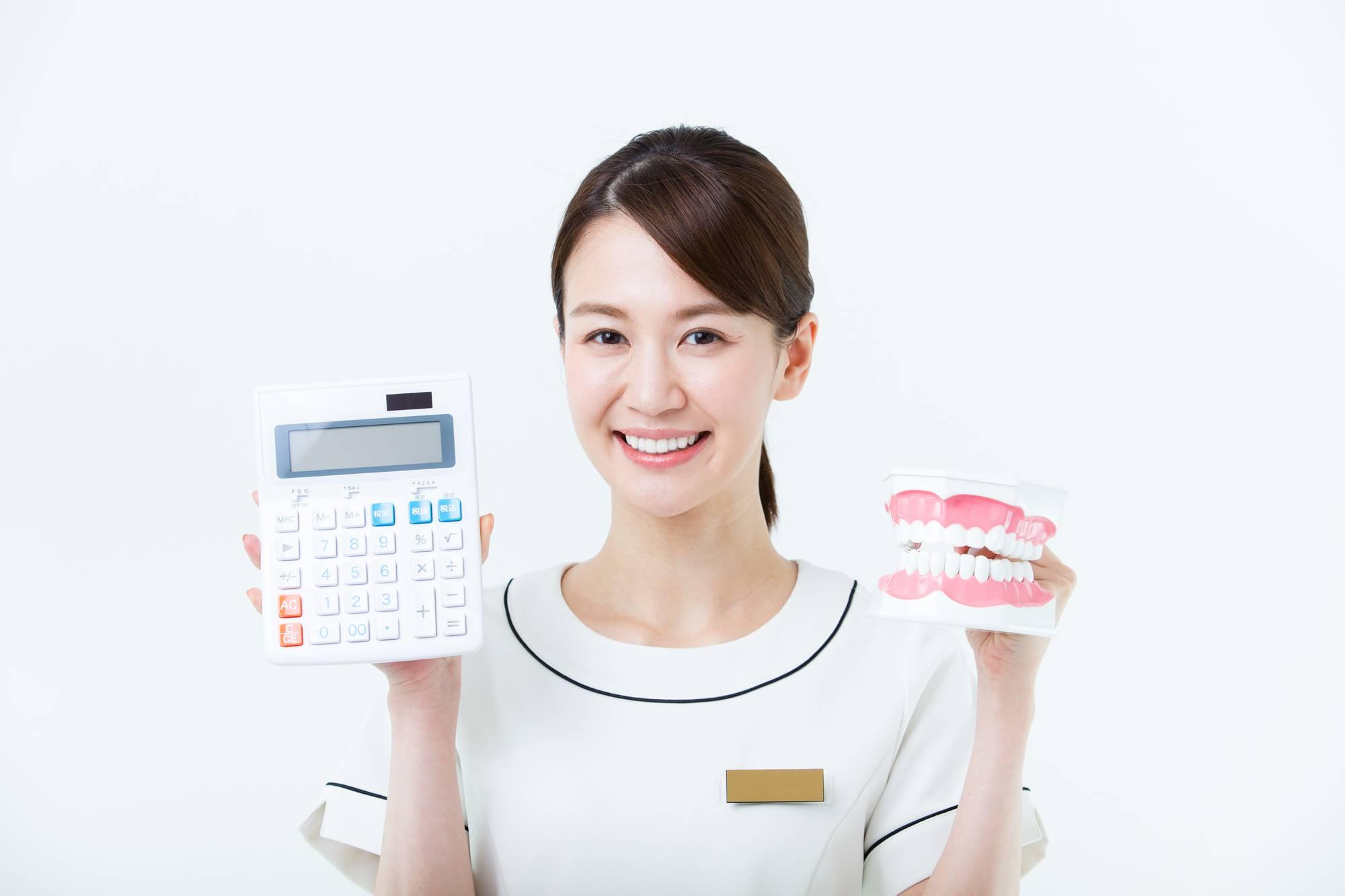 電卓と歯の模型を持つ歯科衛生士