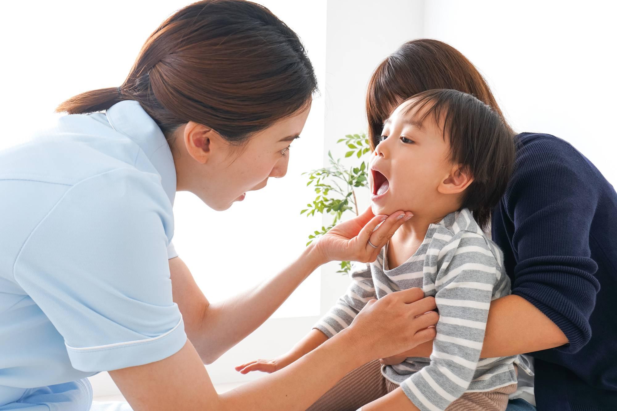 歯科衛生士に口の中を見せる子どもと母親