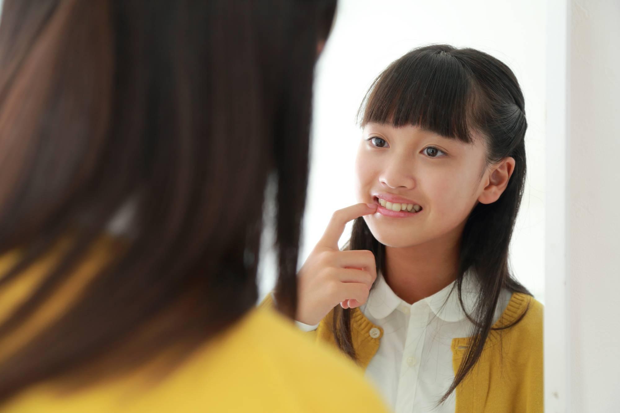鏡で歯をチェックする女の子