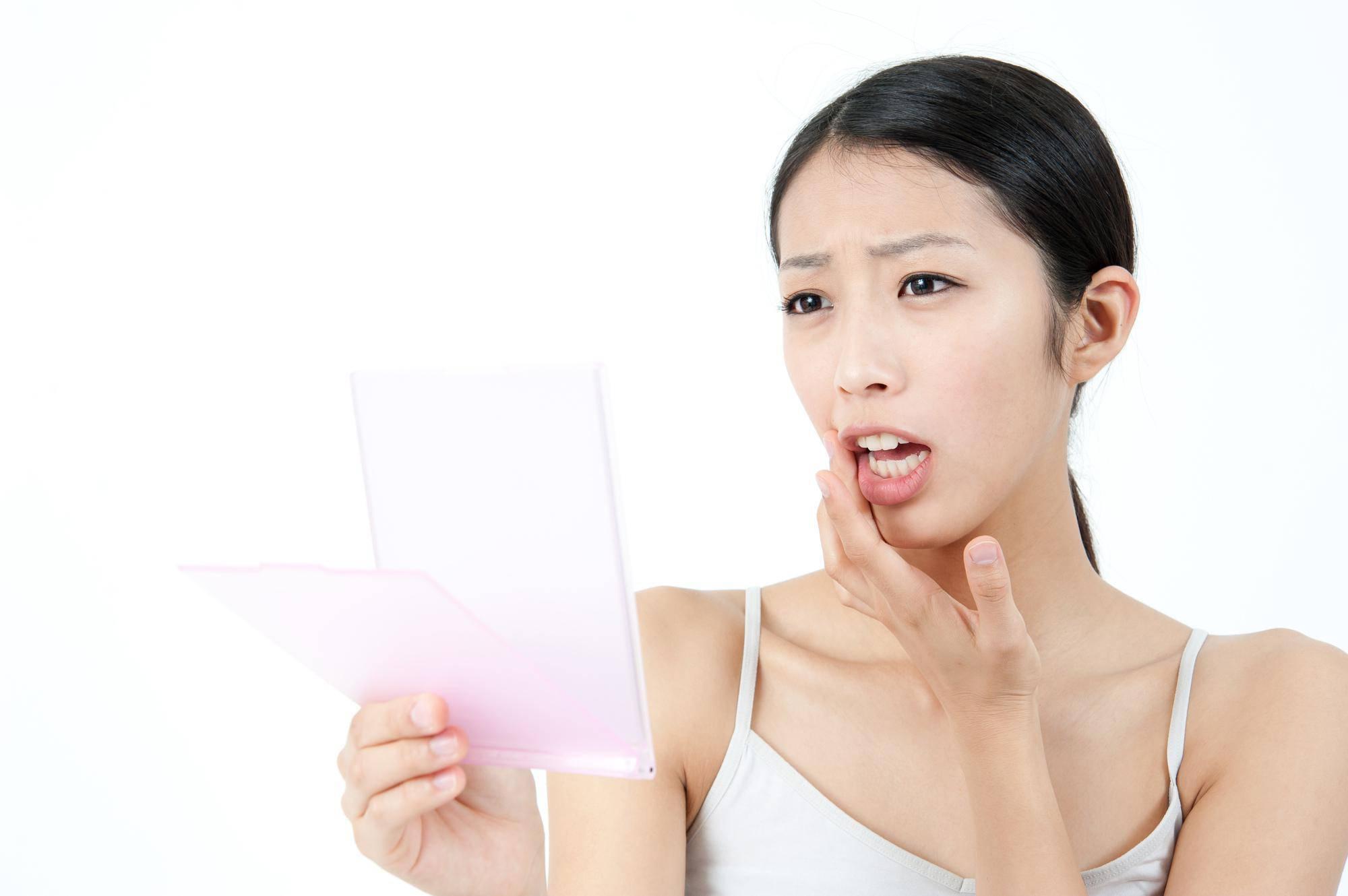 歯茎の腫れを鏡で見る女性