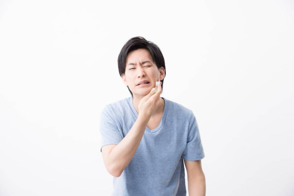 口内に痛みを感じる男性の写真