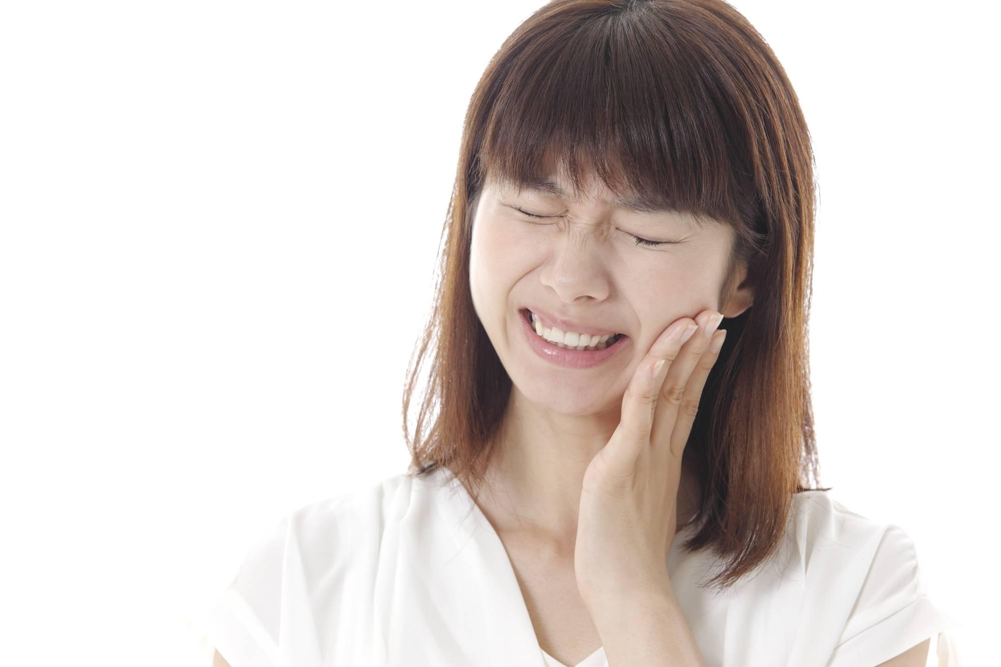 顎に激痛が走る女性