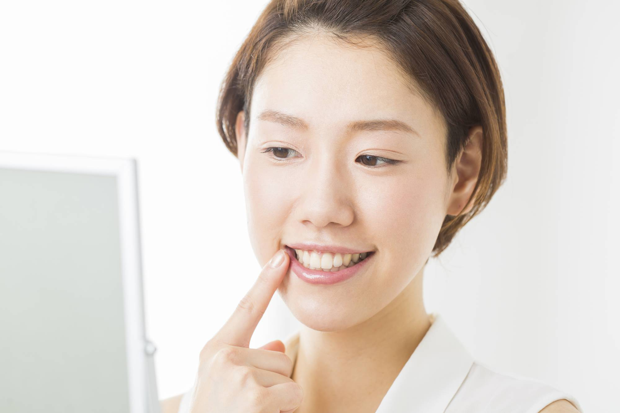 鏡で歯をチェックする女性
