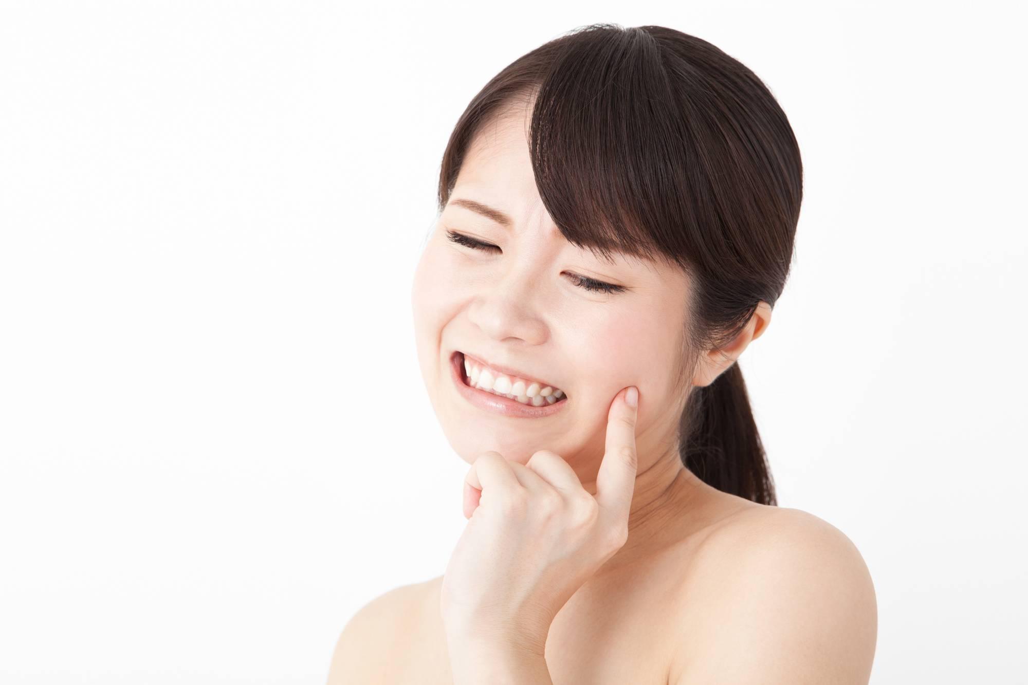 歯茎に口内炎ができて痛がる女性