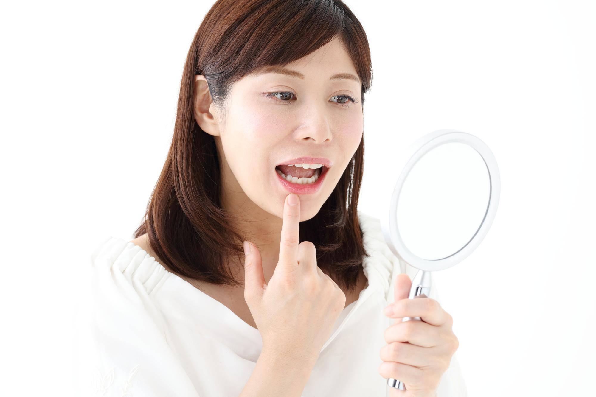 口の中を鏡でチェックする女性